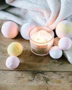 scented candles surrounded by bath bombs