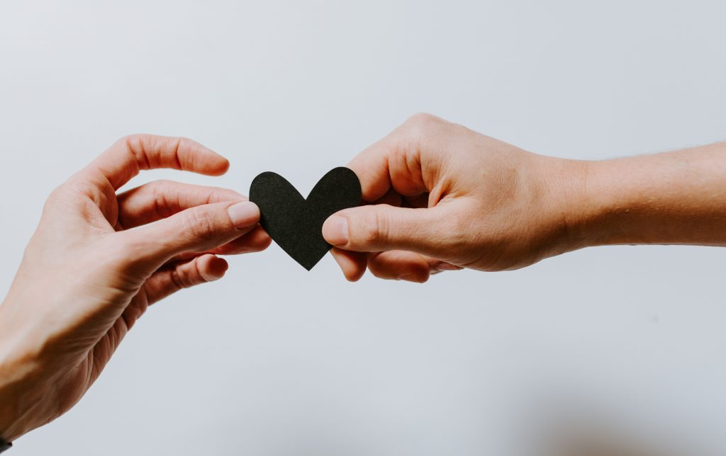 Two hands holding a paper heart